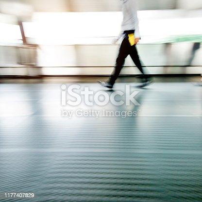 171150458 istock photo Businessman walking on city footbridge 1177407829