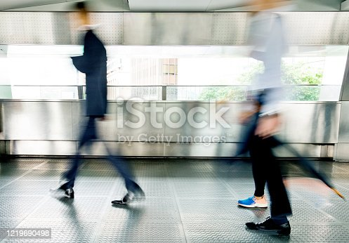 171150458 istock photo Businessman walking on city footbridge 1219690498