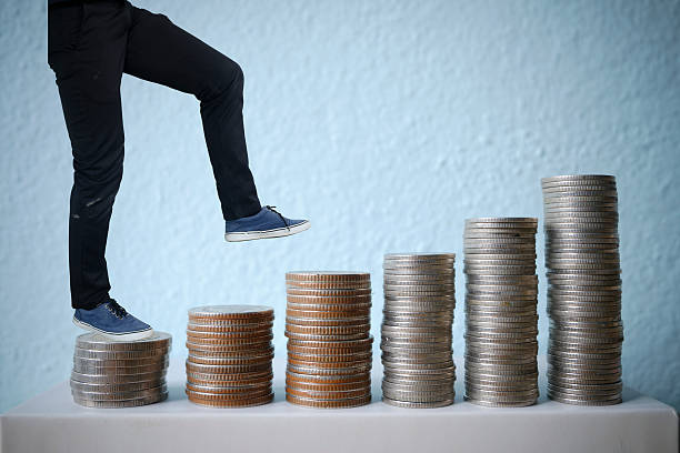 businessman walking on coins stair. business idea concept stock photo