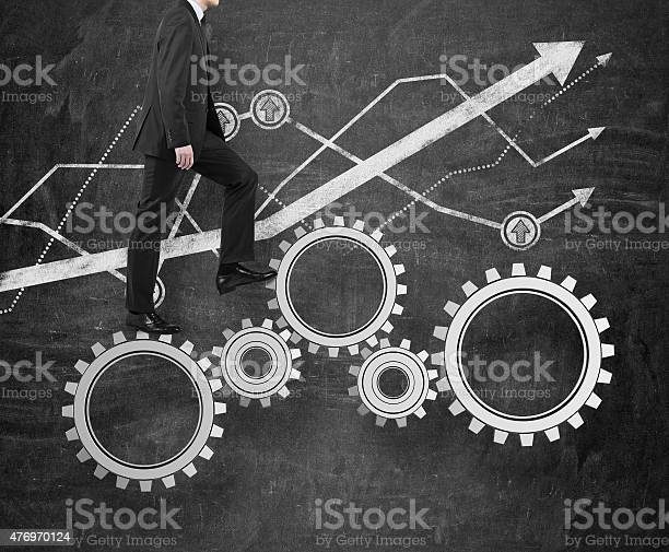 Businessman Walking On Gears Stock Photo - Download Image Now