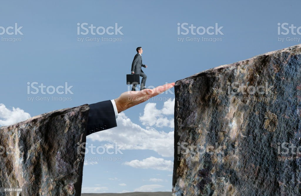 Businessman Walking On Hand That Bridges The Gap stock photo