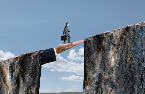 Businessman Walking On Hand That Bridges The Gap stock photo