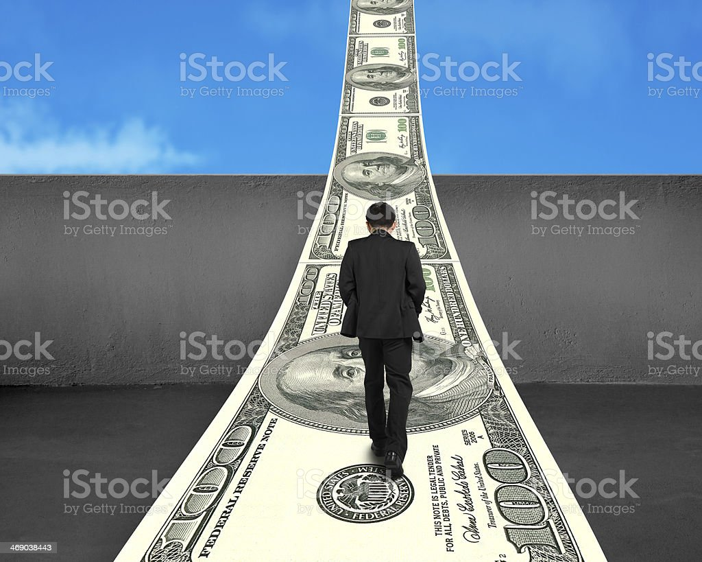 Businessman walking on money way over concrete wall stock photo