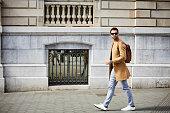 Full length of businessman walking on sidewalk. Male professional is wearing smart casuals. He is in city.
