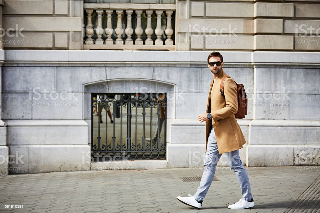 Businessman walking on sidewalk by building - foto de stock
