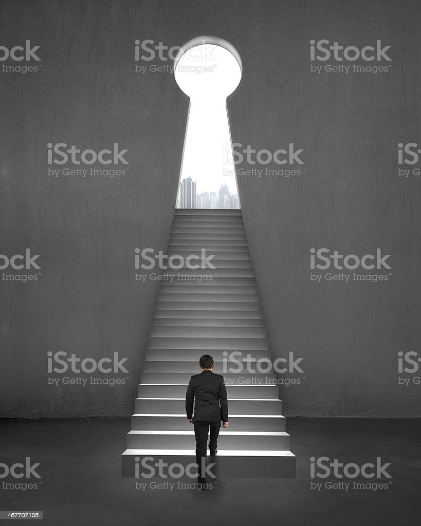 Businessman walking on stair to key shape door, city view stock photo