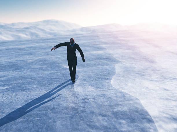 Businessman walking on thin ice stock photo