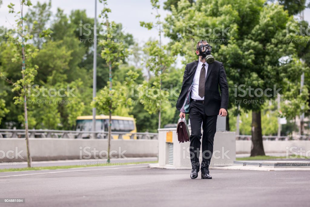 Businessman walking outdoor with briefcase wearing a gas mask on the face. stock photo