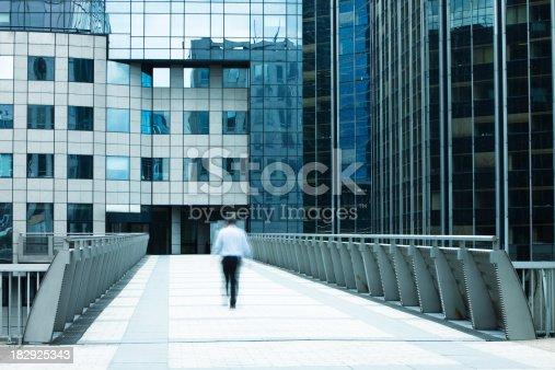 889637894 istock photo Businessman Walking Over Skywalk Toward Office Building, La Defense, Paris 182925343