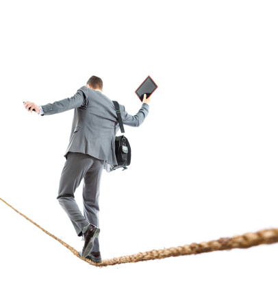 A young businessman holding mobile phone and tablet computer walking the tightrope balancing himself.
