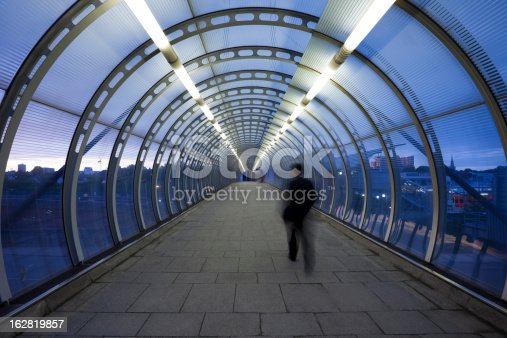 business commuter on urban elevated walkway at dusk, London, UK,