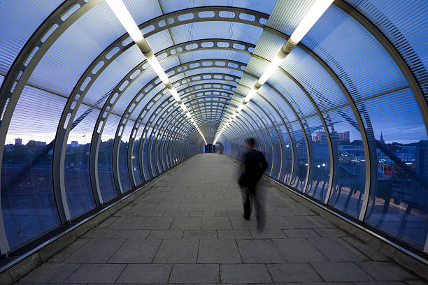 Businessman Walking Through Glass Skywalk at Twilight business commuter on urban elevated walkway at dusk, London, UK, vanishing point stock pictures, royalty-free photos & images