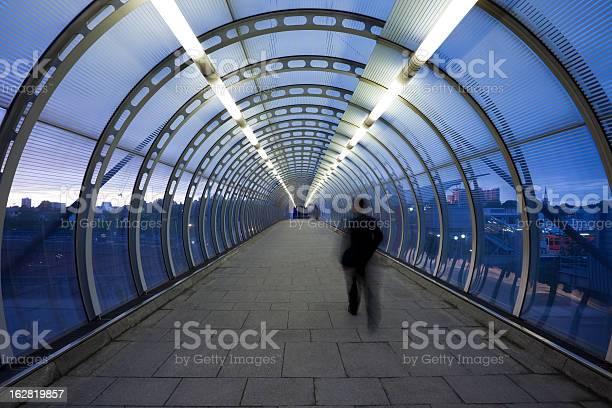 Photo of Businessman Walking Through Glass Skywalk at Twilight