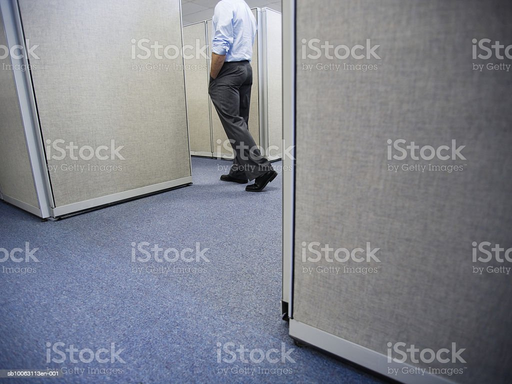 Businessman walking through office cubicle photo libre de droits