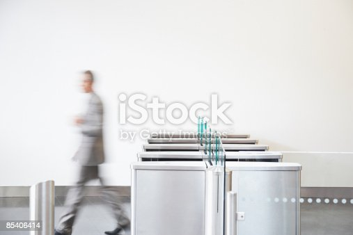 istock Businessman walking through turnstile 85406414