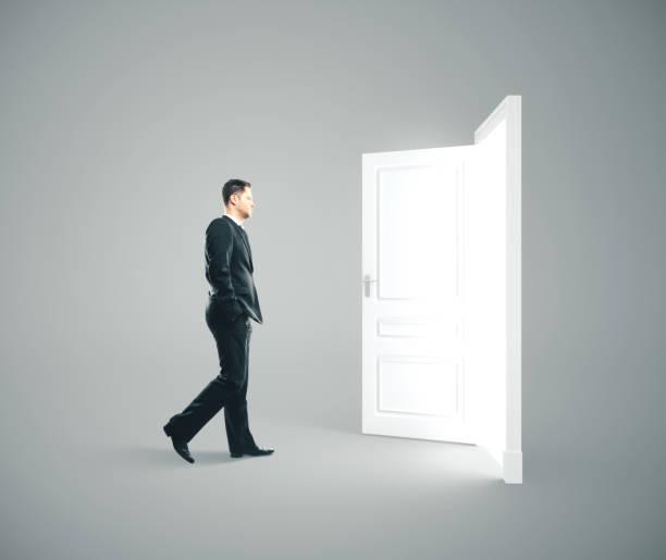 Businessman walking to opened door. stock photo