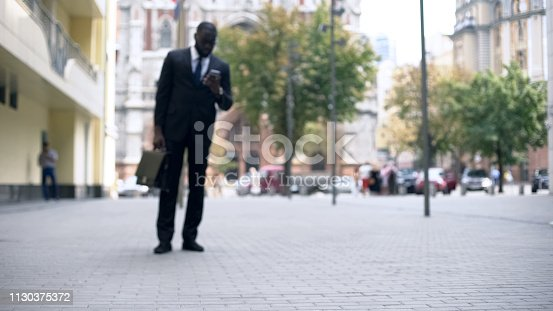 istock Businessman walking to work and using smartphone, busy lifestyle in big city 1130375372