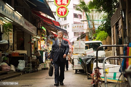 Senior Asian businessman walking to work in the alleys of Hong Kong