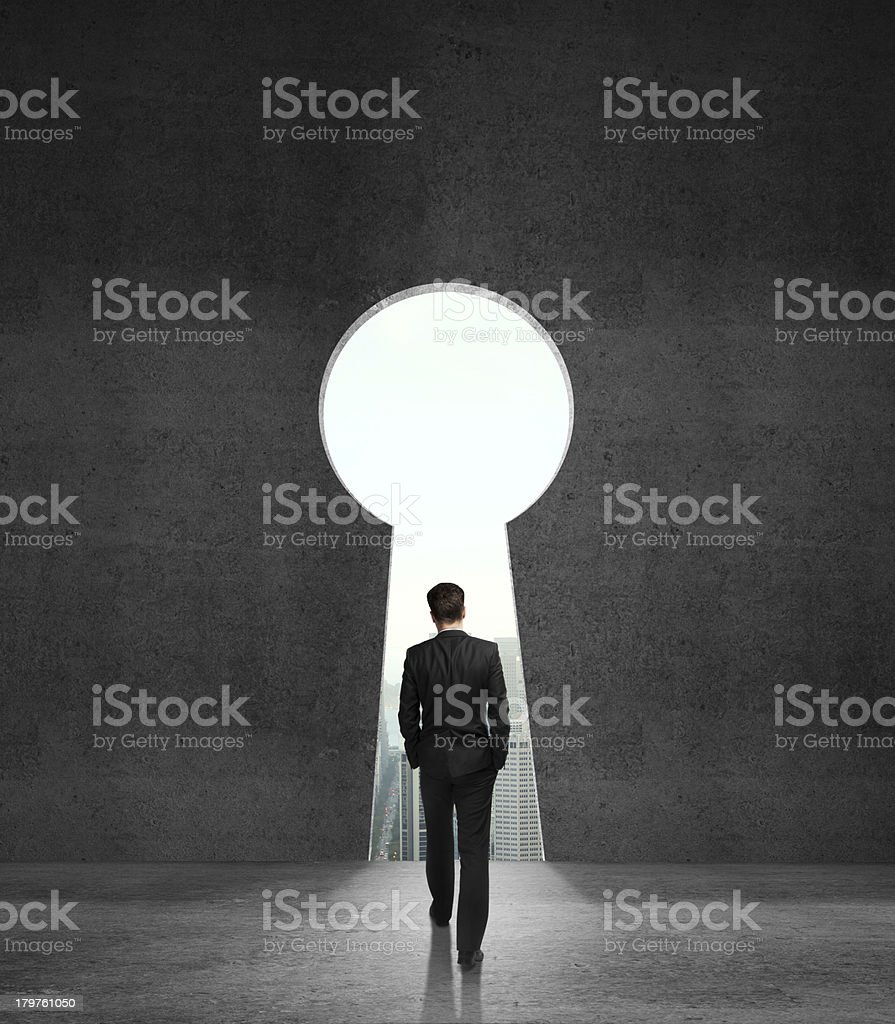 Businessman walking towards a keyhole stock photo