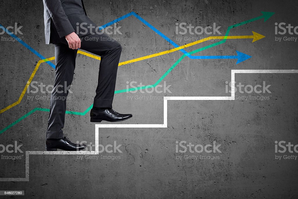 Businessman walking up staircase with colorful line graph stock photo