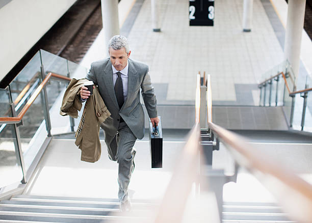 businessman walking up stairs in train station - moving up stock photos and pictures
