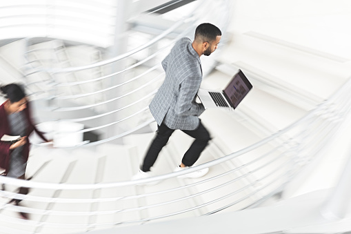 684803840 istock photo Businessman walking up stairs 1141324606