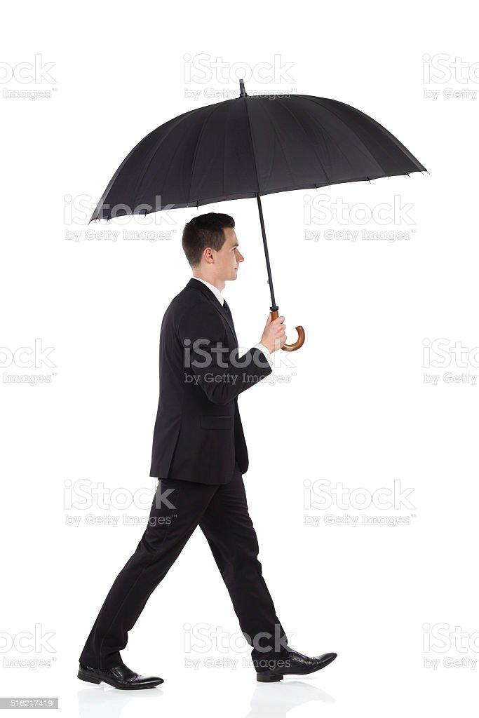 Businessman walking with an umbrella stock photo
