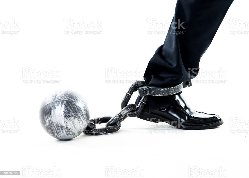 Businessman walking with ball and chain stock photo