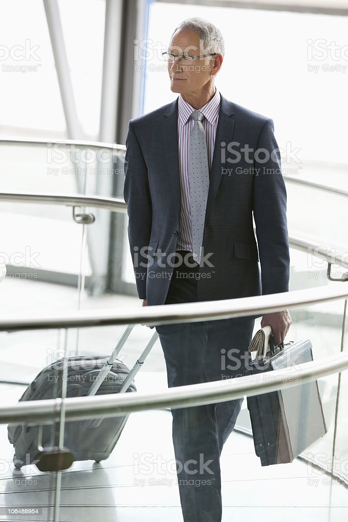Businessman walking with briefcase and luggage in corridor royalty-free stock photo