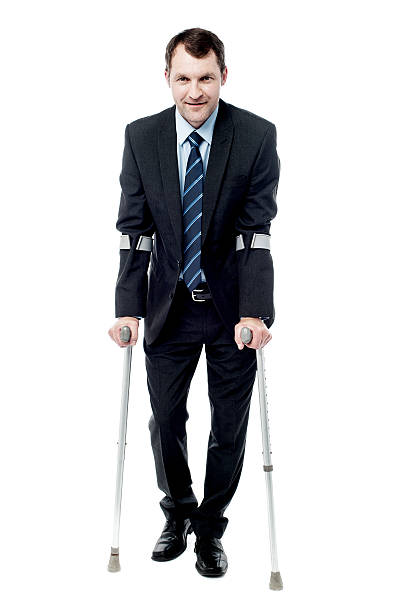 Businessman walking with crutches stock photo