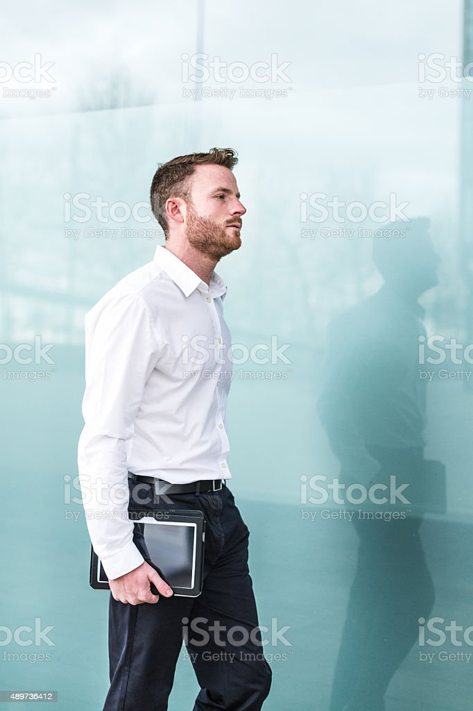 Businessman walking with digital tablet stock photo