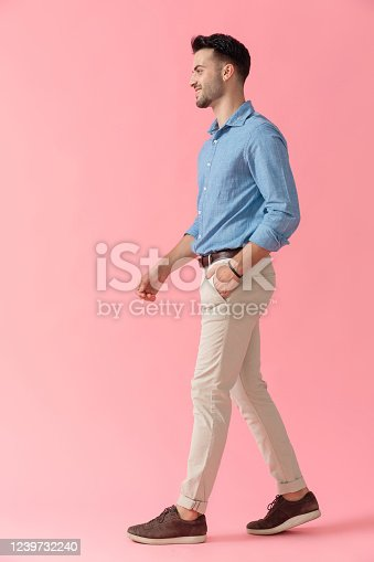 side view of a young businessman wearing blue shirt walking with hand in pocket and looking ahead happy on pink studio background