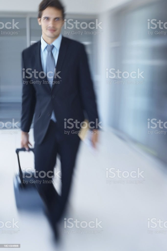 Businessman walking with his luggage at the airport royalty-free stock photo