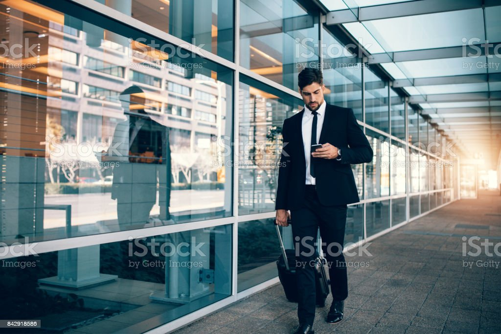 Businessman walking with luggage and using mobile phone at airport stock photo