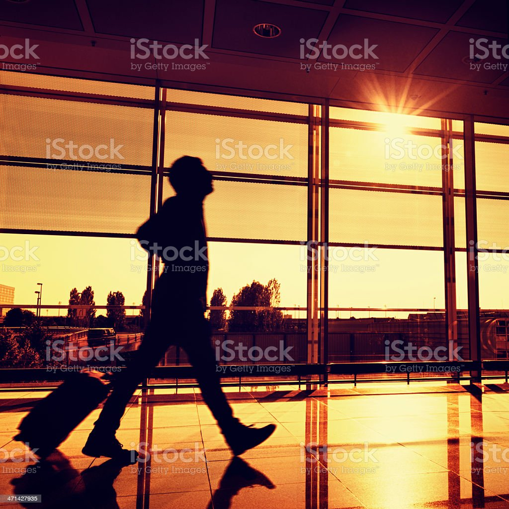 Businessman walking with luggage on airport royalty-free stock photo