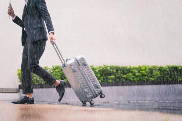 Geschäftsmann zu Fuß mit Gepäck am Regentag – Foto