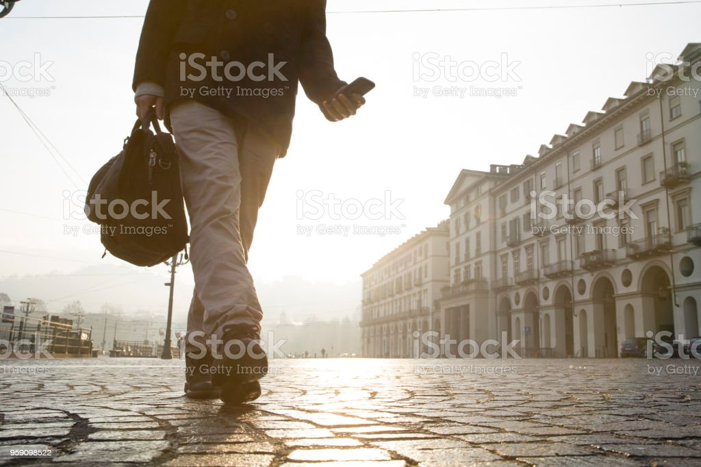 Businessman walks across cobblestones in Piazza San Vittorio, Turin stock photo
