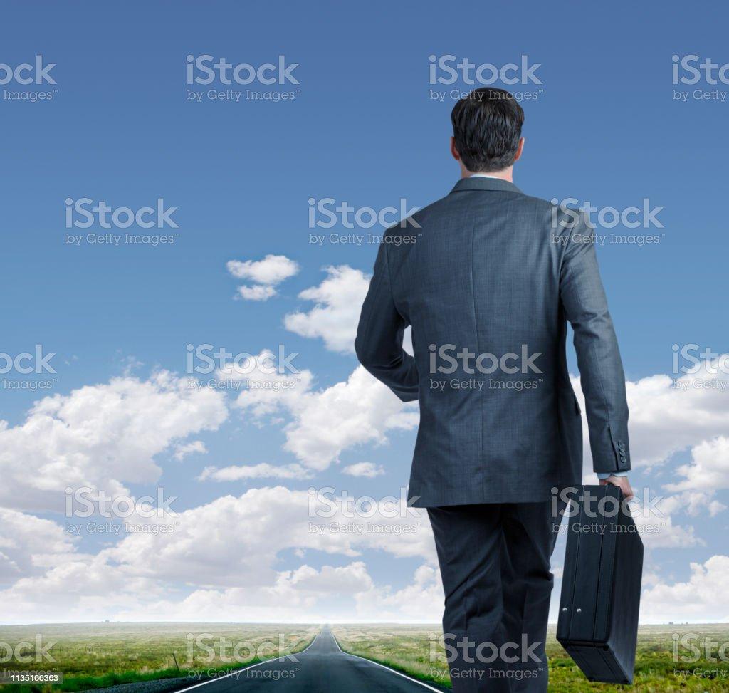 Businessman Walks Down Long Road Toward The Horizon stock photo