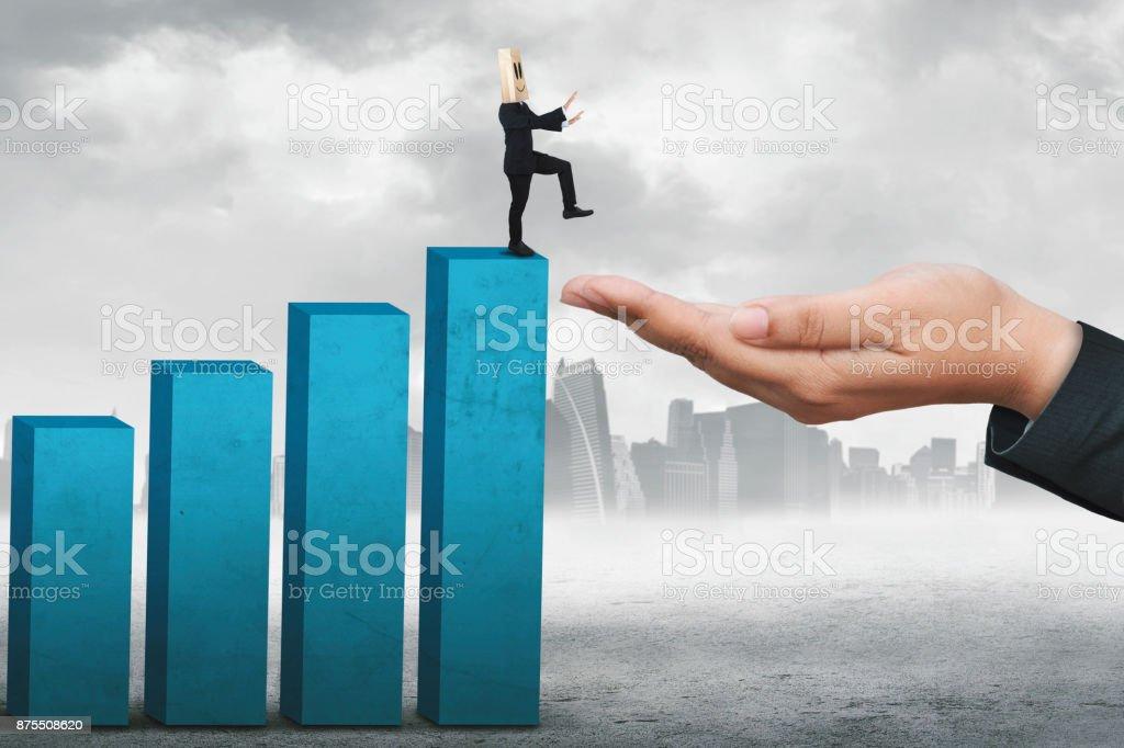 Businessman walks toward a helping hand stock photo