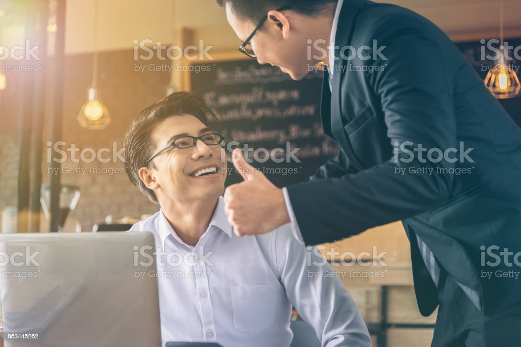Businessman was given a thumbs-up and compliments from his boss who successfully worked. stock photo