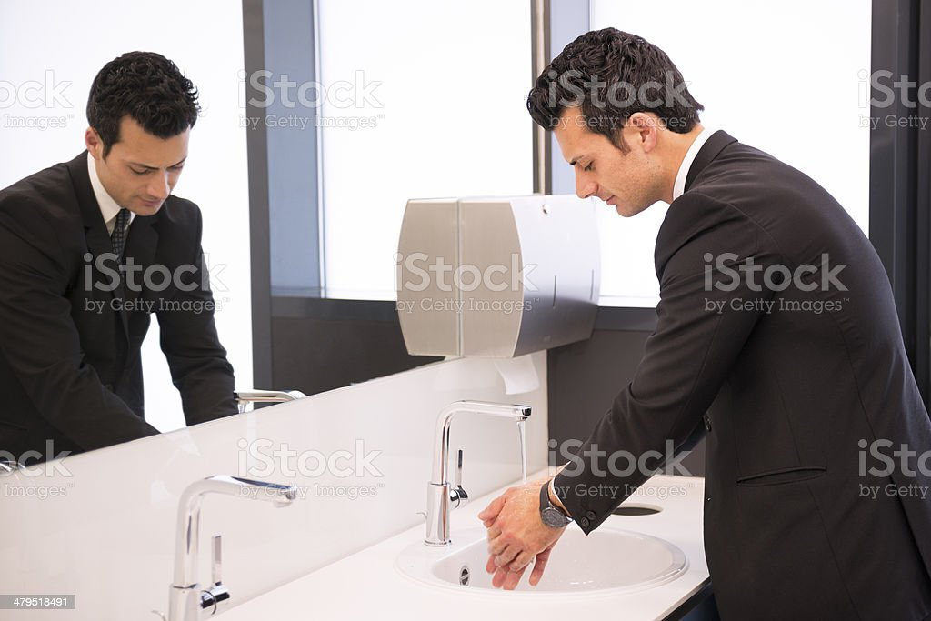 businessman washing his hands at restroom stock photo