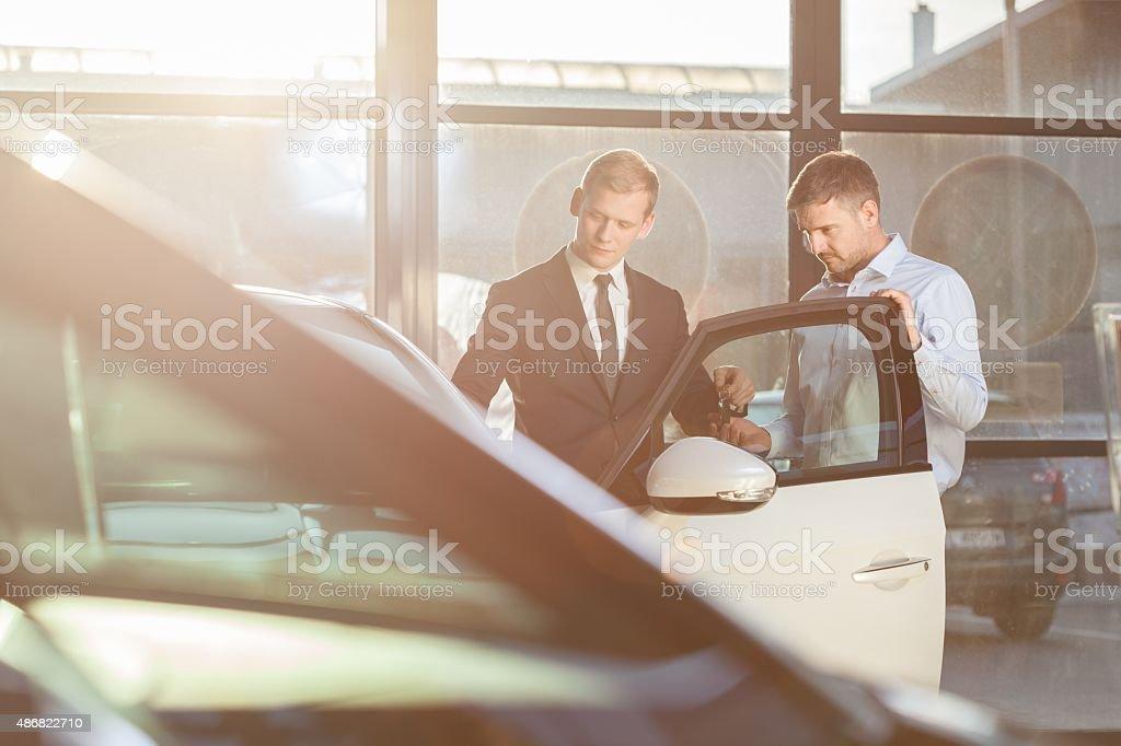 Businessman watching car in showroom Handsome mature businessman watching car in showroom 2015 Stock Photo