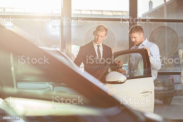 Businessman Watching Car In Showroom Stock Photo - Download Image Now
