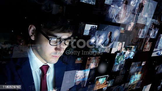 913588258 istock photo Businessman watching hologram screens. Social networking service concept. Streaming video. Video library. 1180529762