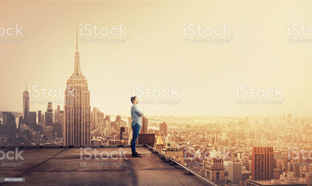 Geschäftsmann, wacht über die große Stadt bei Sonnenuntergang – Foto