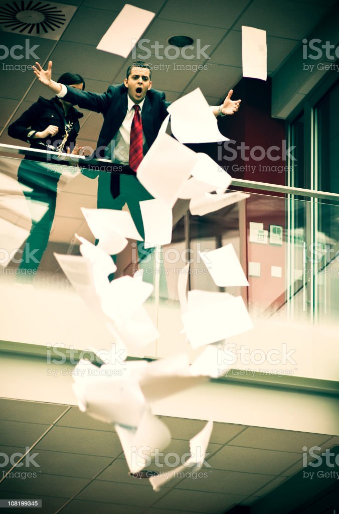 Businessman Watching Papers Fly Over Balcony royalty-free stock photo