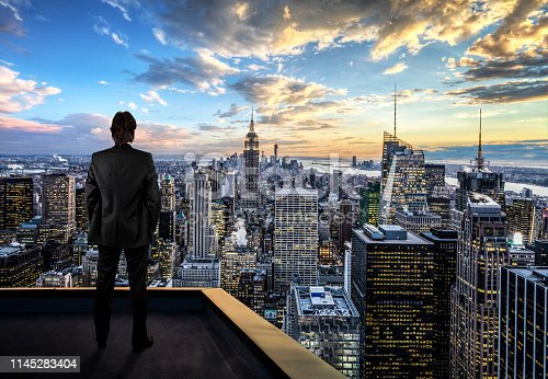 Businessman watching the New York City on the rooftop of skyscraper