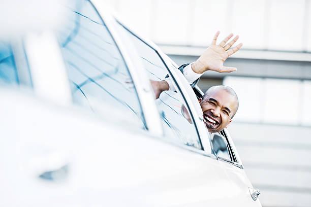 homme d'affaires signe de la main d'une limousine. - homme faire coucou voiture photos et images de collection
