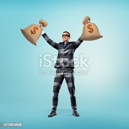 istock A businessman wearing a classic suit with stripes that resembles a burglar's outfit and a black eye mask stands with his arms up holding two bags of cash. 1070604836