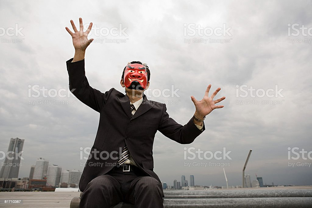 A businessman wearing a devil mask royalty-free stock photo